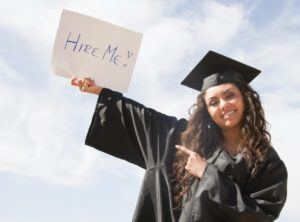 "Graduate holding a sign that says, ""Hire Me!"""