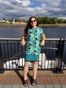 woman in sunglasses and green skirt with water in background