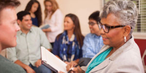 older black woman working with adults in clinic