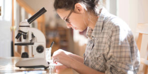 young woman with glasses looking through microscope