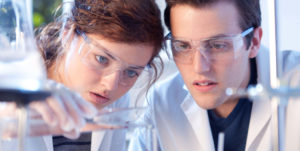 woman and man in lab coats working with test tubes