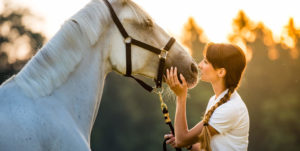 young woman with brown pigtails petting horse
