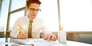man in white shirt and ties working with bar charts