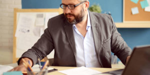 man with beard and glasses looking at financial documents