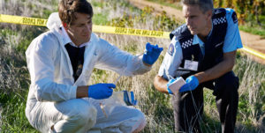 two men wearing protective gloves examine in the field