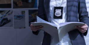 man in blazer with police badge necklace reading file