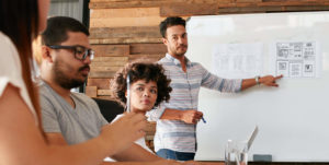 young man with beard at white board instructing group of people