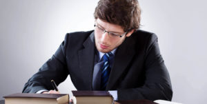 young man writing in legal books