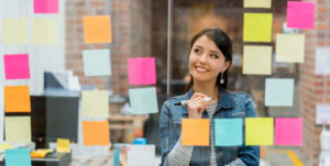young woman thinking with post-it notes