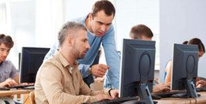 man in blue shirt helping man in tan shirt with computer screen