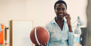 young black woman on phone holding basketball
