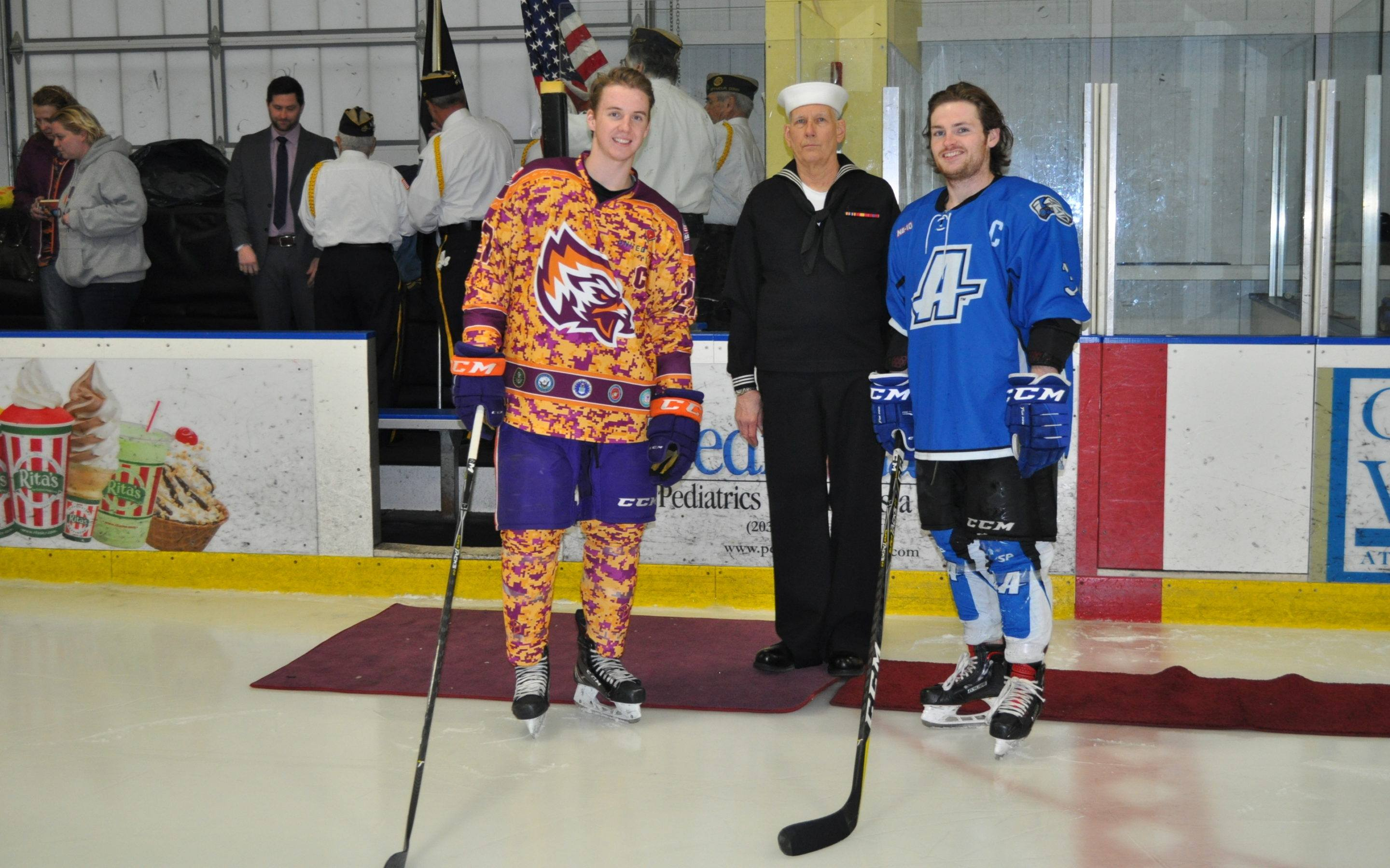 two hockey players and one soldier on ice