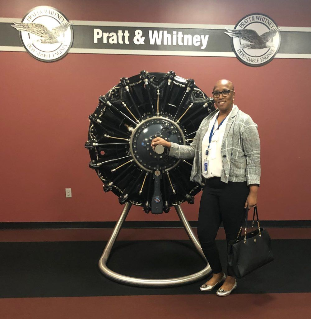 black woman standing next to airplane engine