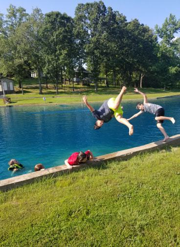 kids jumping into lake