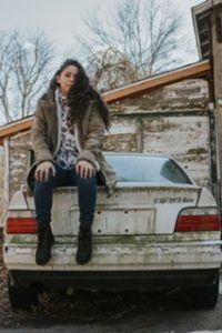 young woman with long brown hair sitting on old white car