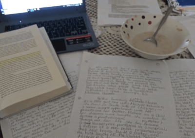 papers and laptop on table next to cereal bowl