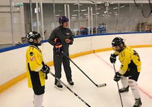 two youth hockey players on ice with man coaching