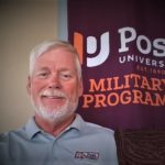 ed in front of Post military poster