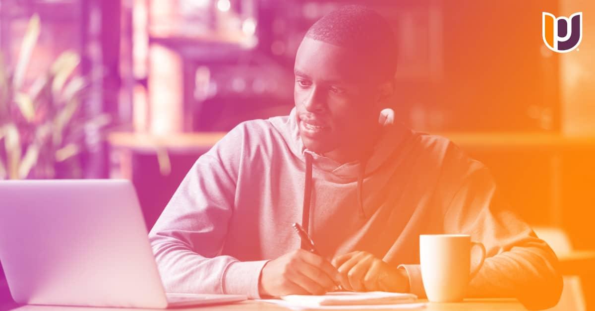 man sitting at desk looking at computer
